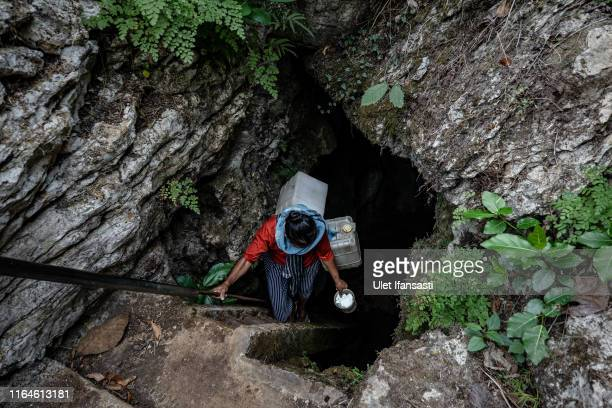 Poniyem walks down the stairs into a cave while carrying jerrycans to get water at Klepu village Sawahan Kulon on August 28 2019 in Pacitan East Java...