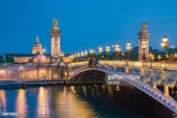 pont alexandre iii over seine river against cloudy sky (dusk) - île de france stock-fotos und bilder