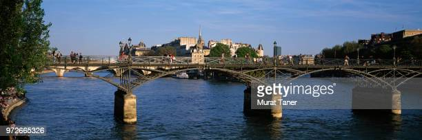 pont des arts bridge spanning the seine river in paris - paris island stock photos and pictures