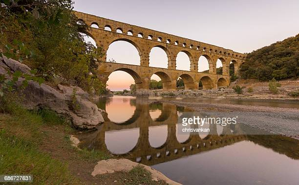 pont du gard aqueduct reflections in gardon river, france - nimes stock pictures, royalty-free photos & images