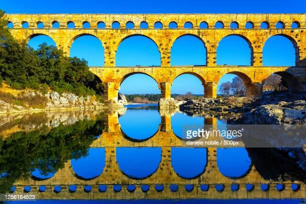 pont du gard reflecting in river, castillon-du-gard, france - ガール県 ストックフォトと画像