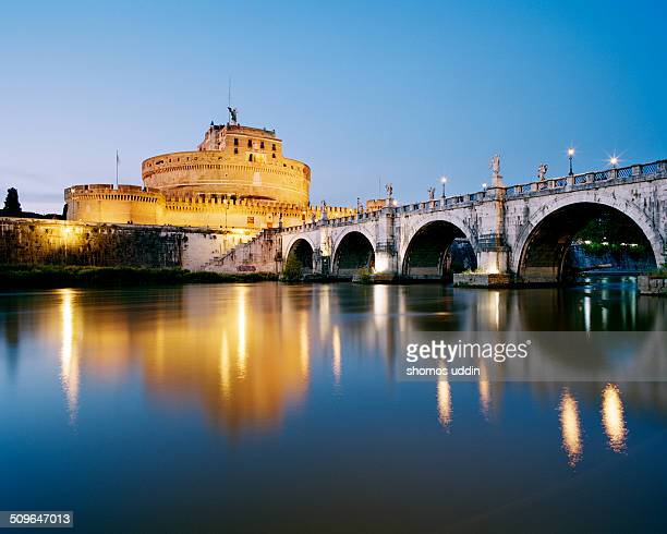 Pont Sant'Angelo and Castle Sant'Angelo reflected in River Tiber at dusk
