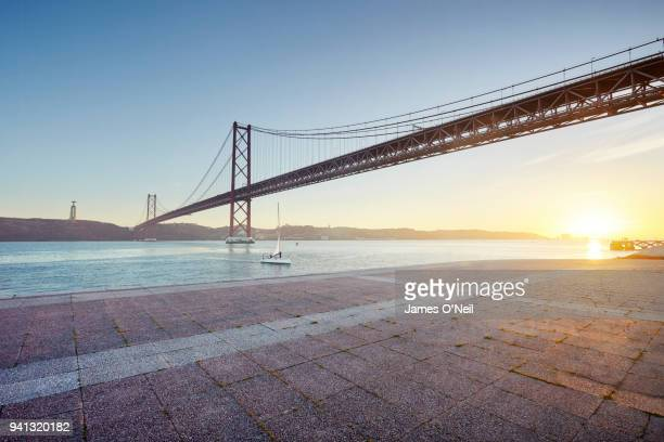 Ponte 25 de Abril at sunset with foreground paving, Lisbon, Portugal