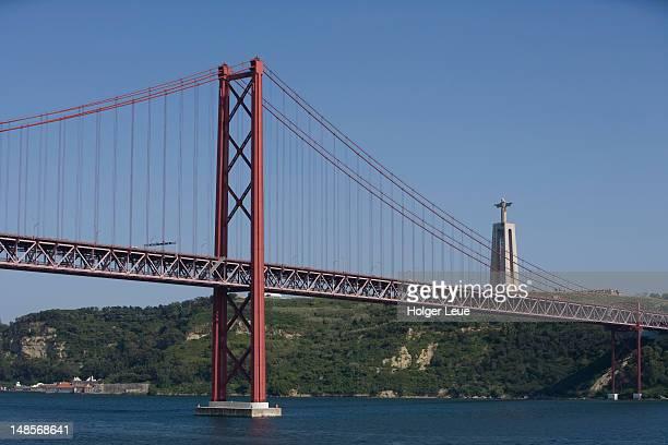 ponte 25 de abril bridge on tagus river and cristo rei statue. - statua di cristo re foto e immagini stock