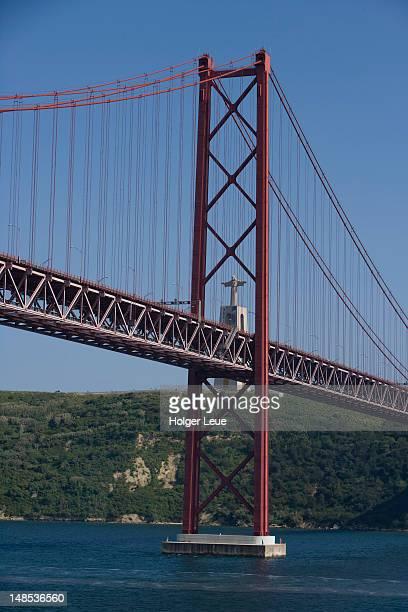 ponte 25 de abril bridge over tagus river and cristo rei statue. - statua di cristo re foto e immagini stock