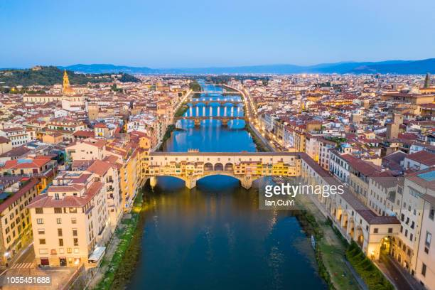 ponte vecchio bridge and the historic city of florence at dusk. (dusk) - florence italy stock pictures, royalty-free photos & images