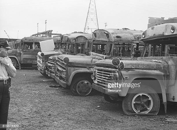 A Pontiac policeman examines some of the ten school buses destroyed late Aug 30 by dynamite and fire in a school bus depot here About 40 other buses...