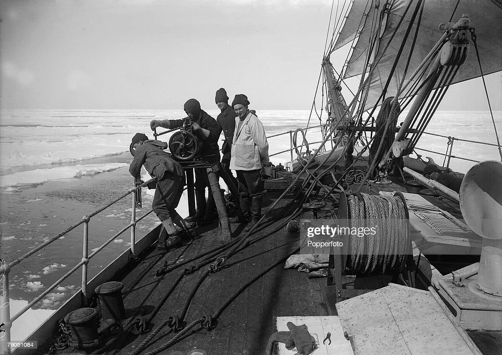 """H.G Ponting. Captain Scott+s Antarctic Expedition 1910 - 1912. 17th December, 1910. Crew members letting down the water bottle over the side of the """"Terra Nova"""" ship into the pack ice. : News Photo"""