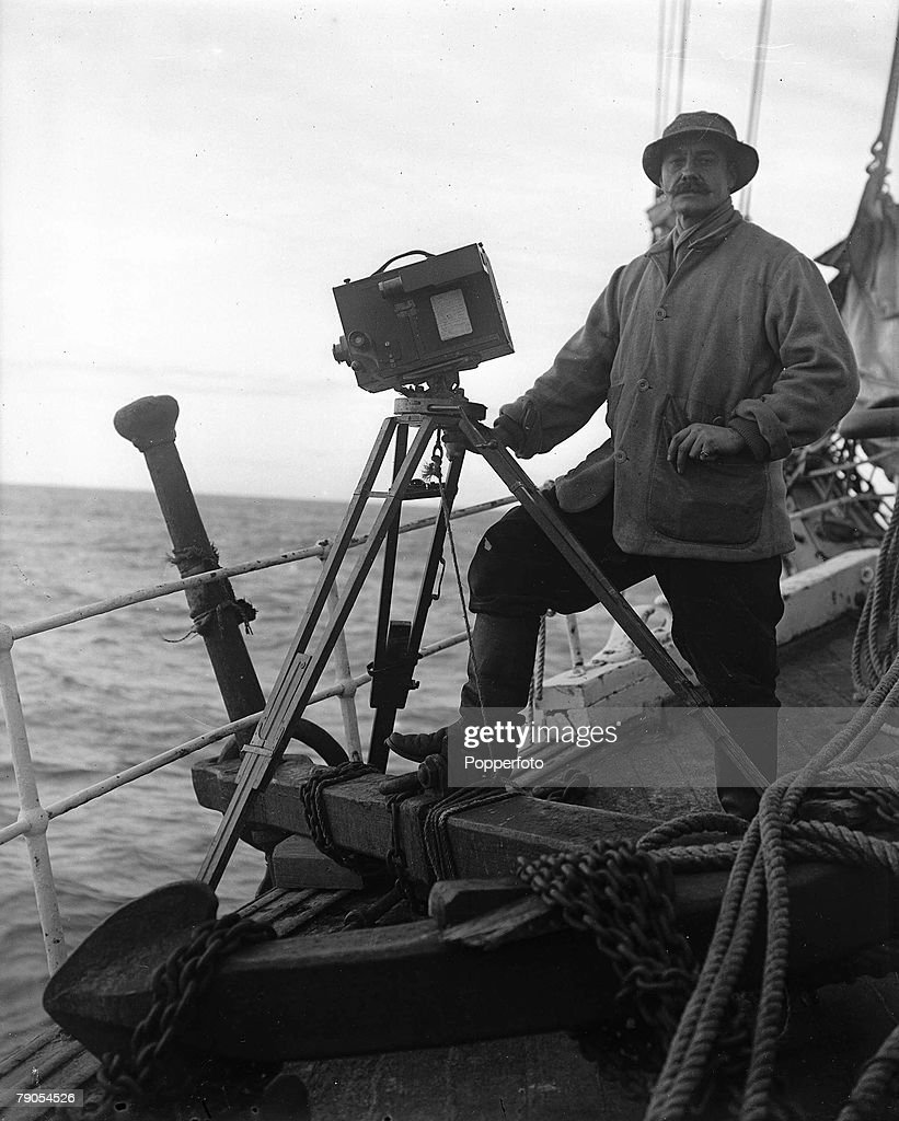 H.G Ponting. Captain Scott+s Antarctic Expedition 1910 - 1912. Photographer Herbert Ponting taking a picture of whales with his camera over the side of the Terra Nova ship : News Photo