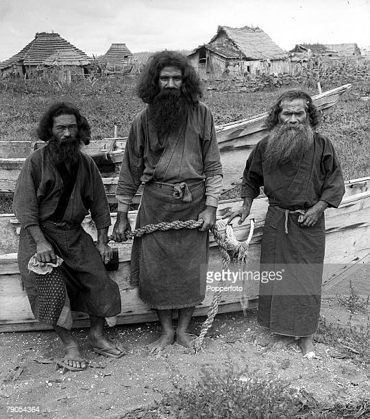 HG Ponting in Asia 1900 1906 Japan Ainu fishermen wearing traditional clothing stand in front of their boat