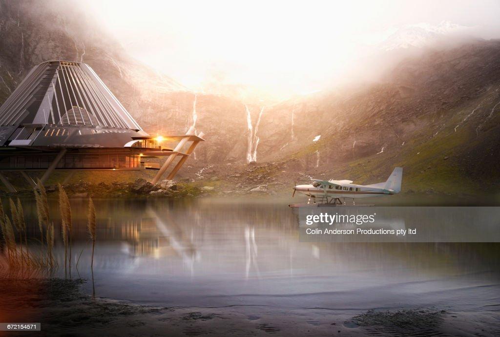 Pontoon airplane on lake near futuristic house : Stock-Foto