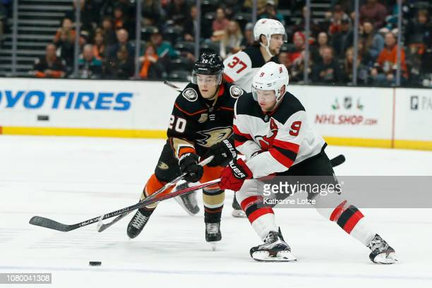 Pontus Aberg of the Anaheim Ducks and Taylor Hall of the New Jersey Devils fight for control of the puck at Honda Center on December 09 2018 in...