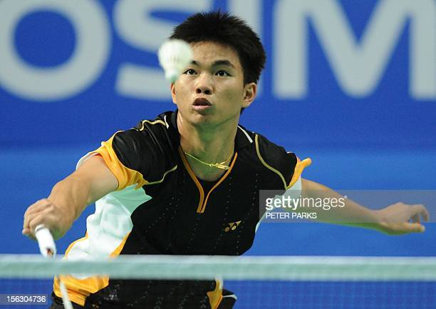 Poodchalat Pisit of Thailand hits a return to Kento Momota of Japan in their men's singles qualifying match at the China Open badminton tournament in...