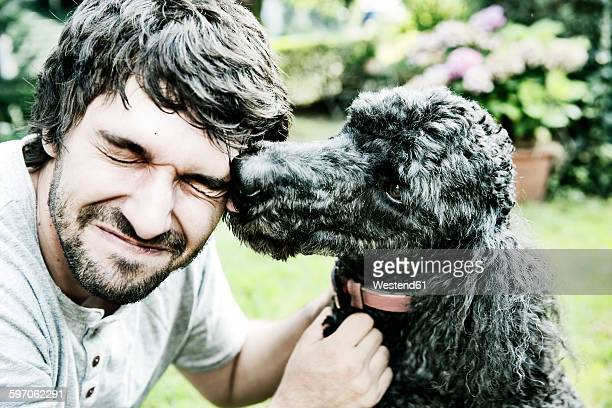 Poodle licking the face of his owner in the garden