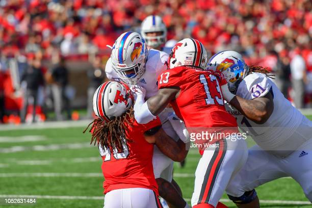 Pooka Williams Jr #1 of the Kansas Jayhawks is stopped at the goal line by Dakota Allen and Kolin Hill of the Texas Tech Red Raiders during the first...