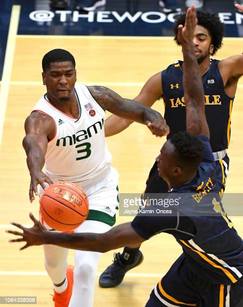 Pookie Powell of and Ed Croswell of the La Salle Explorers guard Anthony Lawrence II of the Miami Hurricanes as he makes a pass under the basket in...