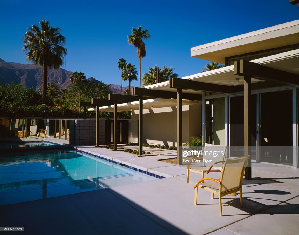 Pool and patio area of modern house with mountains in background stock photo