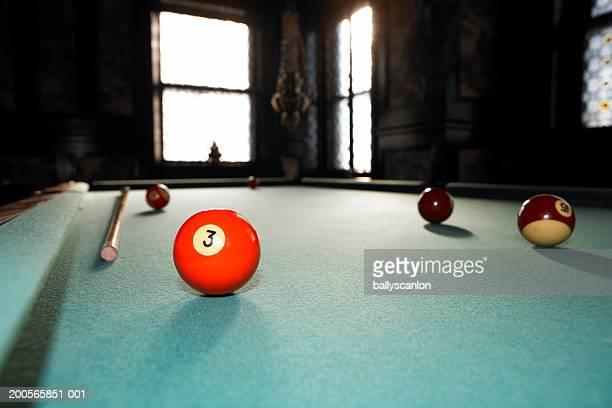 pool balls on pool table in darkened room - number 3 stock pictures, royalty-free photos & images