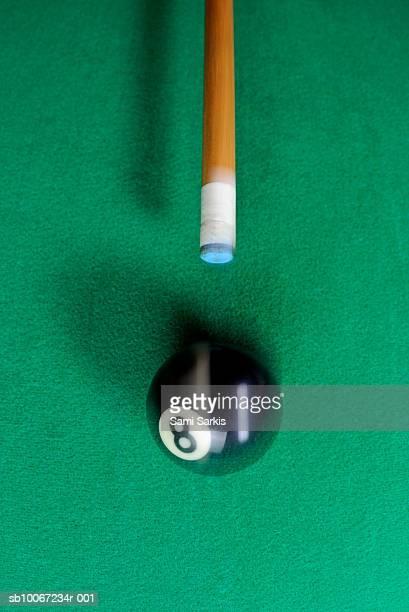 Pool cue striking black ball