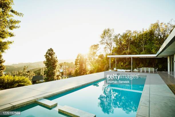 pool in backyard of modern house at sunset - piscine photos et images de collection