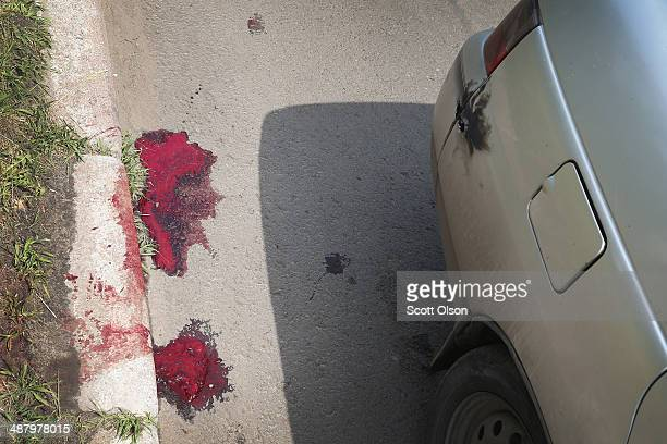 A pool of blood stains the street after two people in a car were hit by gunfire during a firefight between Ukrainian army soldiers and proRussian...