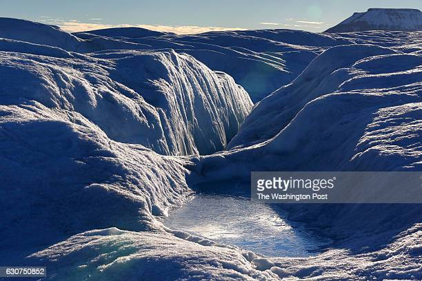 A pool of frozen water rests on the bumpy often wet surface of Petermann glacier on August 27 2016 Petermann's ice shelf broke off a piece roughly...