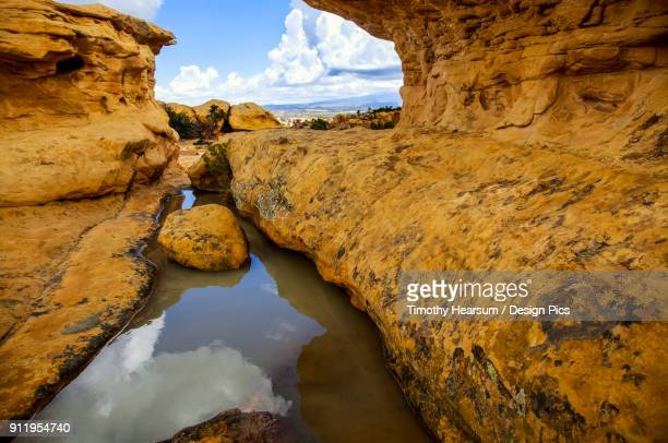 Pool Of Water Trapped By Rocks Reflecting Sky And Clouds In El Malpais National Monument Near Grants, New Mexico In Early Autumn