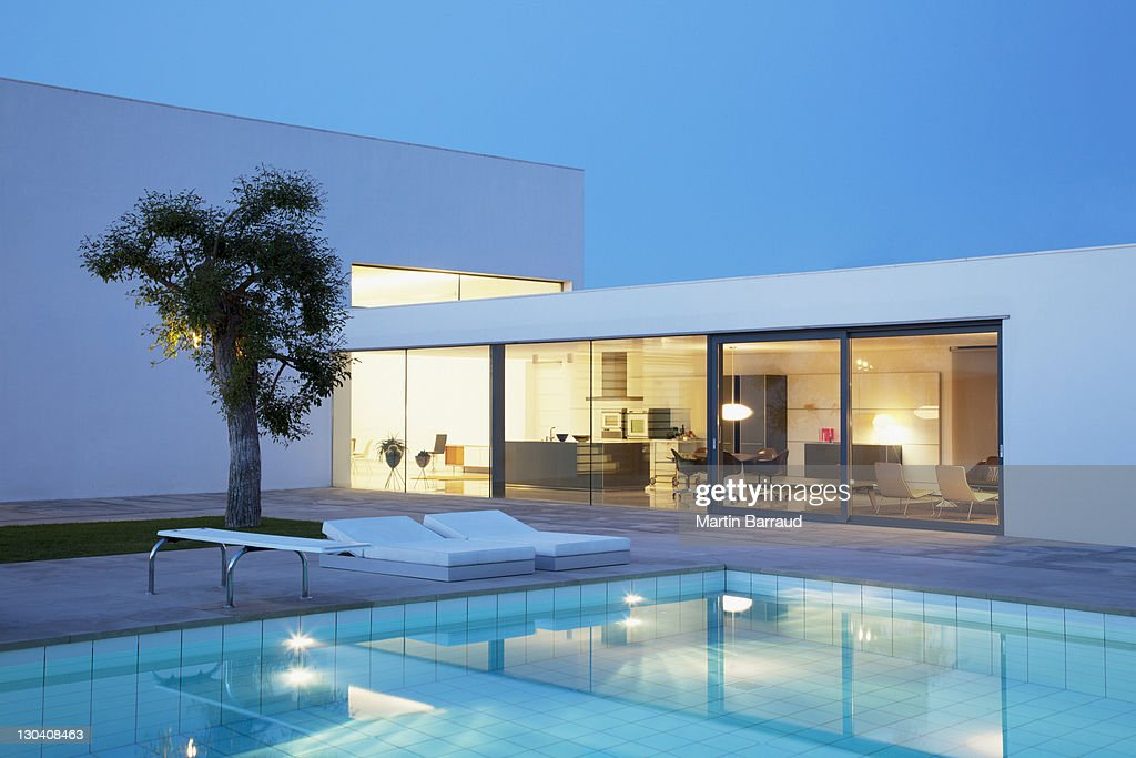 Pool outside modern house at night : Stock Photo