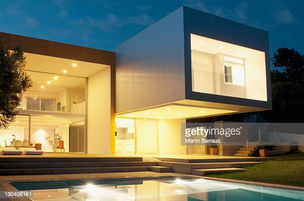 pool outside modern house at twilight - verlicht stockfoto's en -beelden