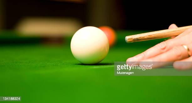 Pool player with cue poised to hit cue ball