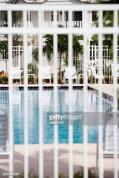 a pool seen through the white painted bars of a safety fence - dana white stock pictures, royalty-free photos & images