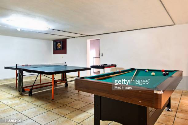 pool table and ping pong table in basement - man cave stock pictures, royalty-free photos & images