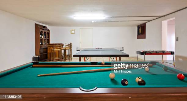 pool table and ping pong table in basement - basement stock pictures, royalty-free photos & images