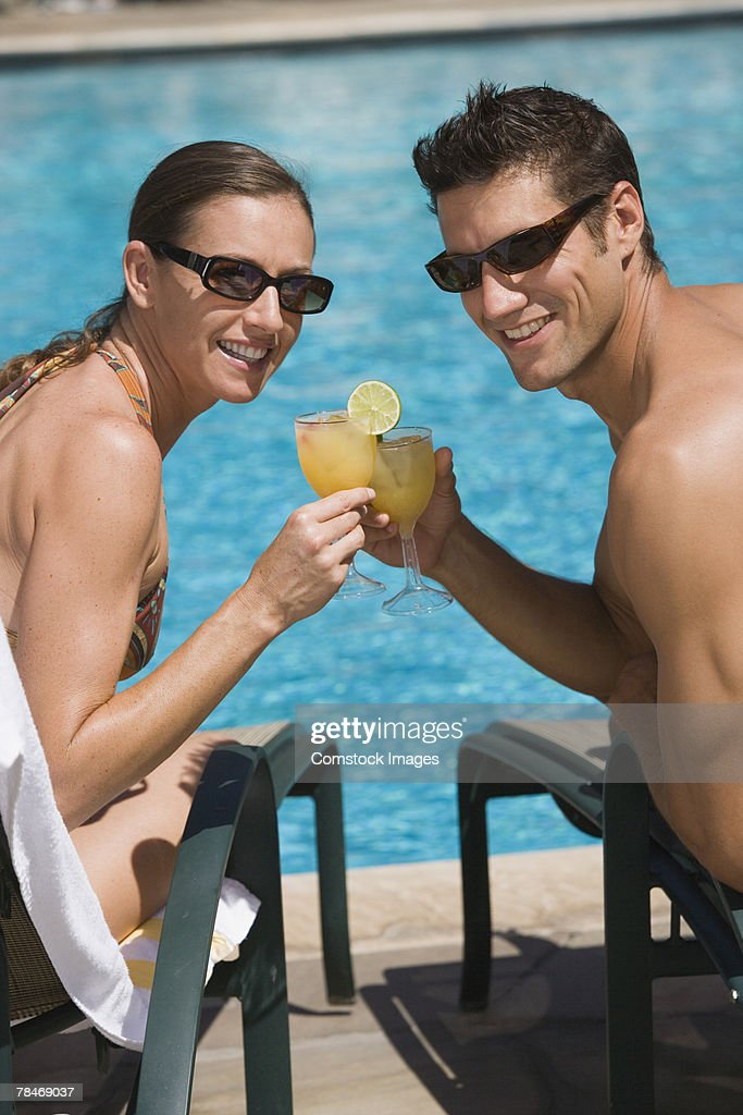 Poolside couple with cocktails : Stock Photo