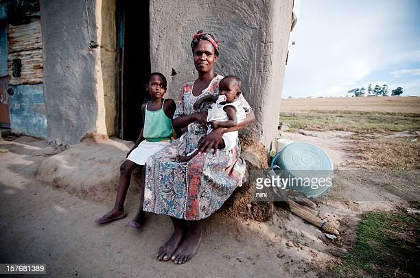 Poor African family sitting in front of a shanty hut