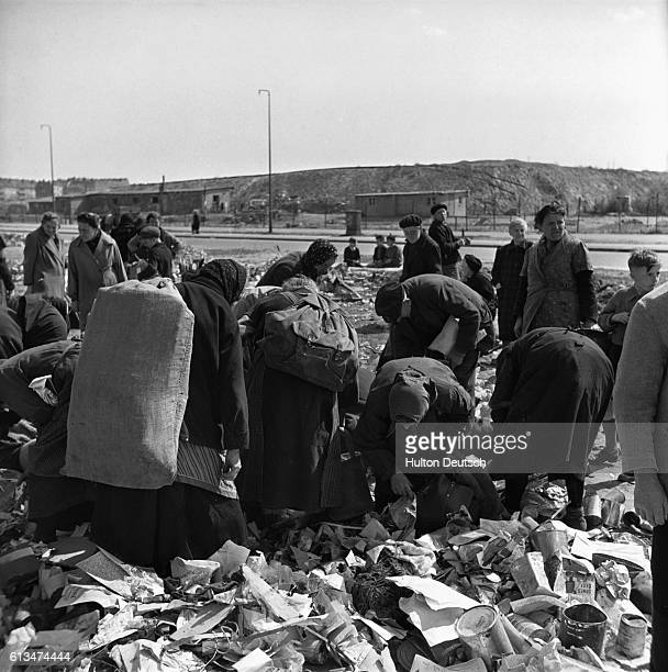 Poor and homeless people, suffering the after effects of World War II, dig through refuse at a dump for their next meal in Berlin in 1946.