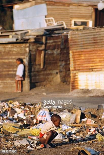 A poor black child crouches to defecate in a garbage pile outside shacks in Alexandra township near the whites only suburbs of Johannesburg South...