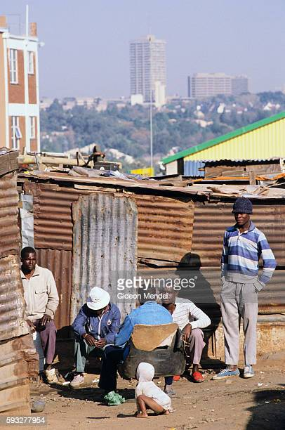 Poor black South Africans sit among shacks in Alexandra Township with a view of the wealthy white suburb of Sandton City in Johannesburg South Africa