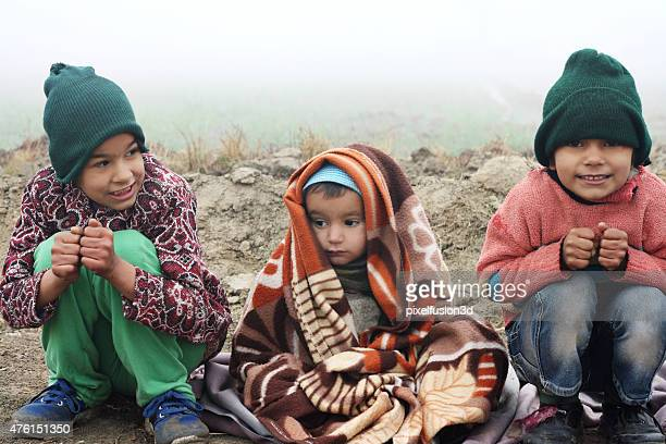 Poor Children Sitting in Winter Season