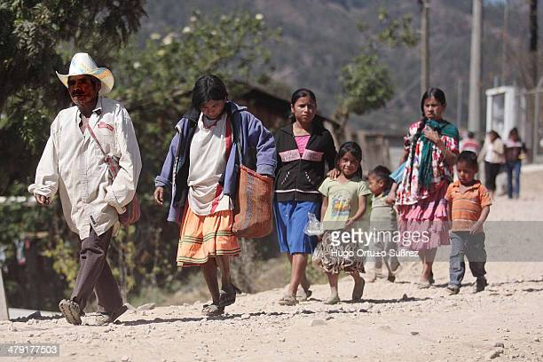 A poor family with old dirty clothes walks down a stone path on a sunny January day in the poorest municipality in Latin America Located in the...