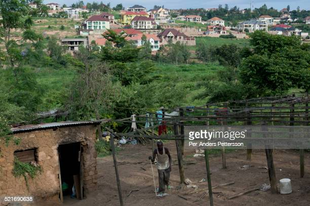A poor farmer lives next to a newly constructed exclusive housing community on November 8 2014 in central Kigali Rwanda The country is one of the...