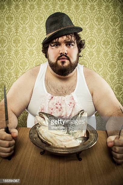 Pauvre gros homme manger la soupe de poisson de la tête sur une table en bois