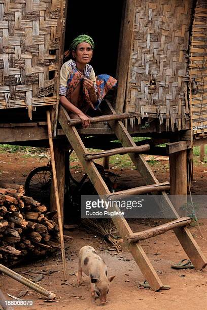Poor house and woman in a tribal village of Rattanakiri
