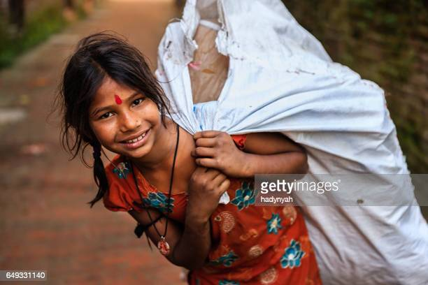 Poor Indian girl collecting plastic bottles for recycling