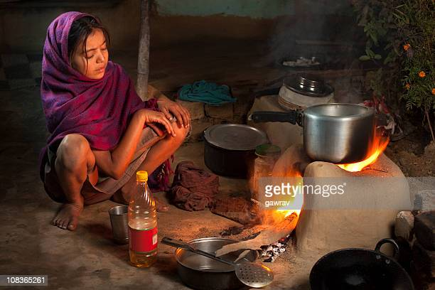 Poor, Indian girl cooking food on a clay stove