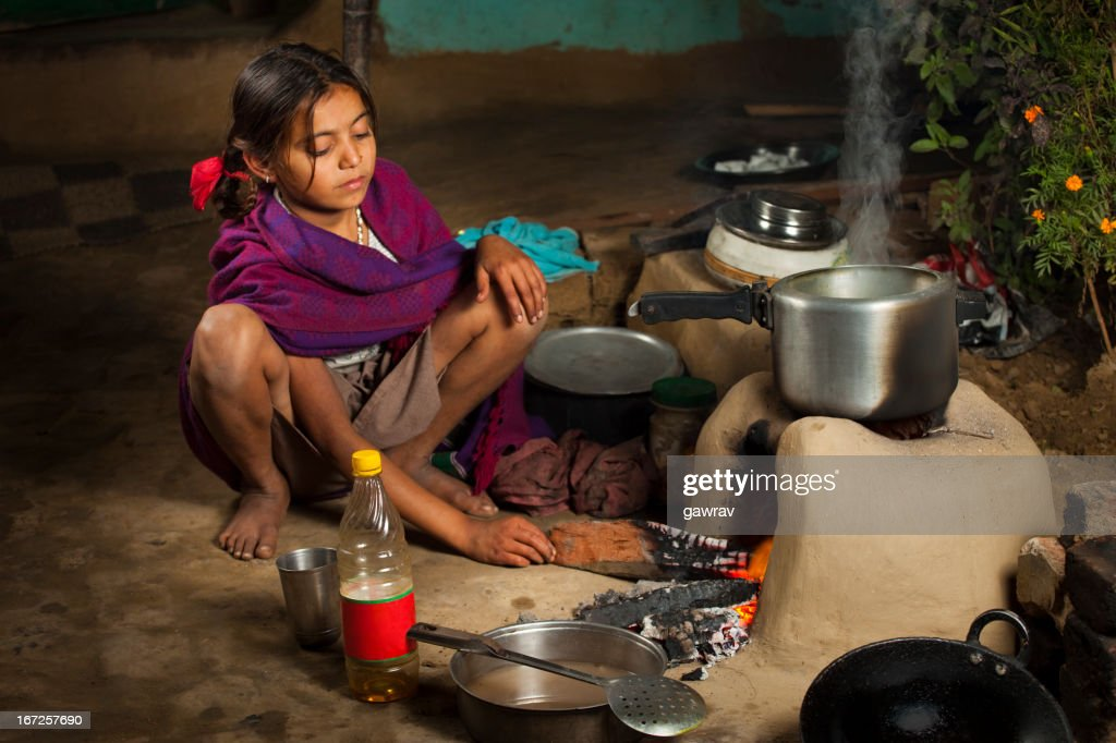 Poor, Indian girl cooking food on a clay stove : Stock Photo