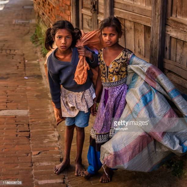 poor indian girls collecting plastic bottles for recycling - child labor stock pictures, royalty-free photos & images