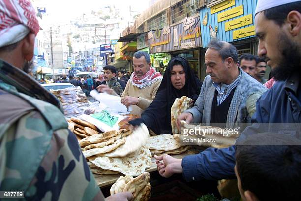 Poor Jordanians collect bread donated by a store December 15 2001 on the last day of the holy month of Ramadan in Amman Jordan