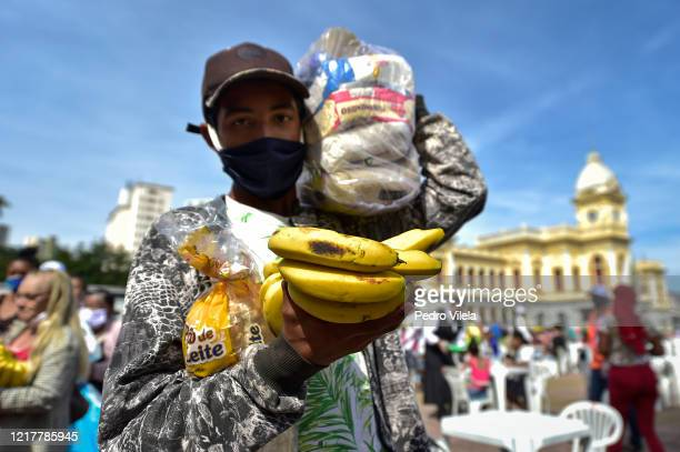 Poor man carrying fruit poses for a photo at Praça da Estação on June 5, 2020 in Belo Horizonte, Brazil. About 3000 meals are being distributed every...