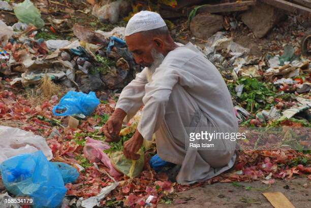 A poor man colleting food items from trash here in port city Karachi